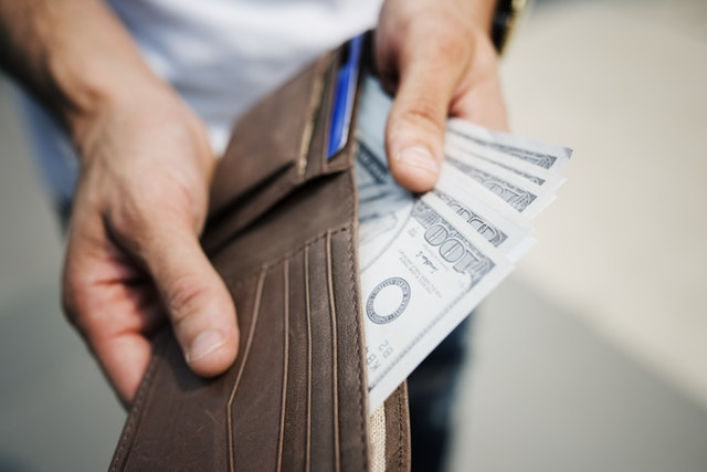 man holding wallet and cash
